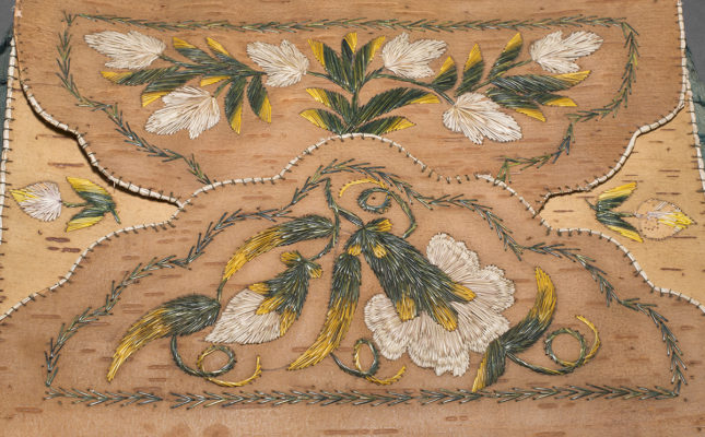 Detail of the top of the case with floral embroidery